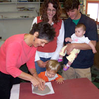Family creating a child's handprint in ceramic clay